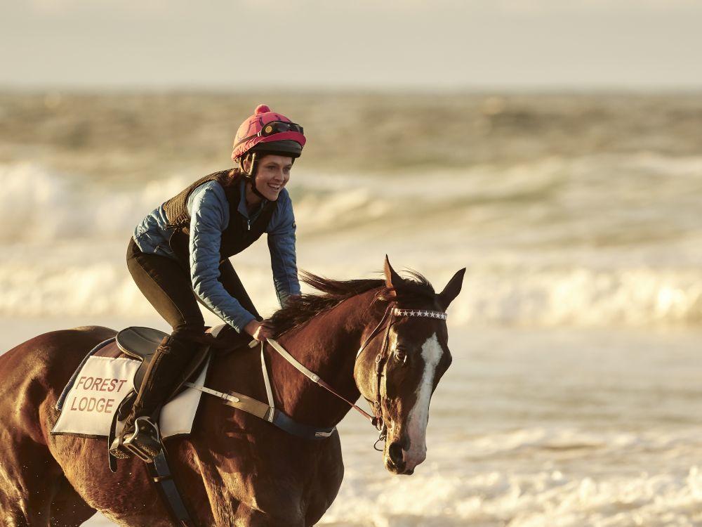 """Teresa Palmer como Michelle Payne entrenando en las playas de Australia en un fotograma de """"Corre como una chica""""."""