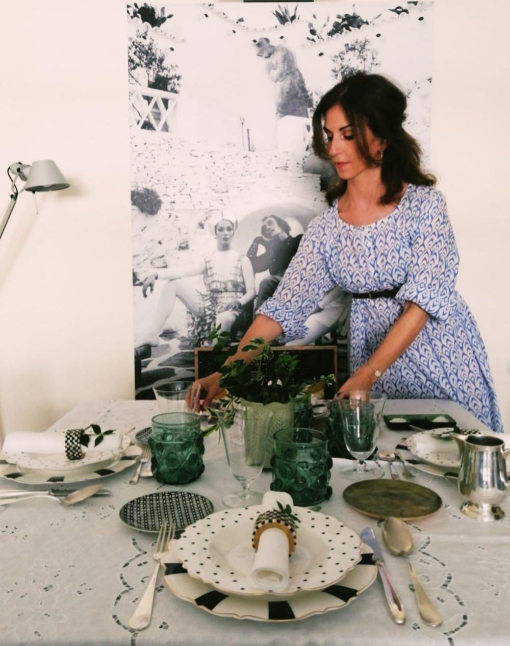 Lucía Francesch, colocando la mesa con mantel blanco de Ibiza y vajilla bicolor.