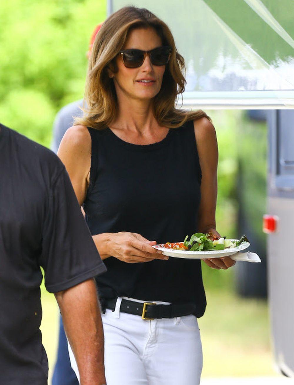 Cindy Crawford con una ensalada con rúcula, verdura de hoja verde que favorece un abdomen plano.