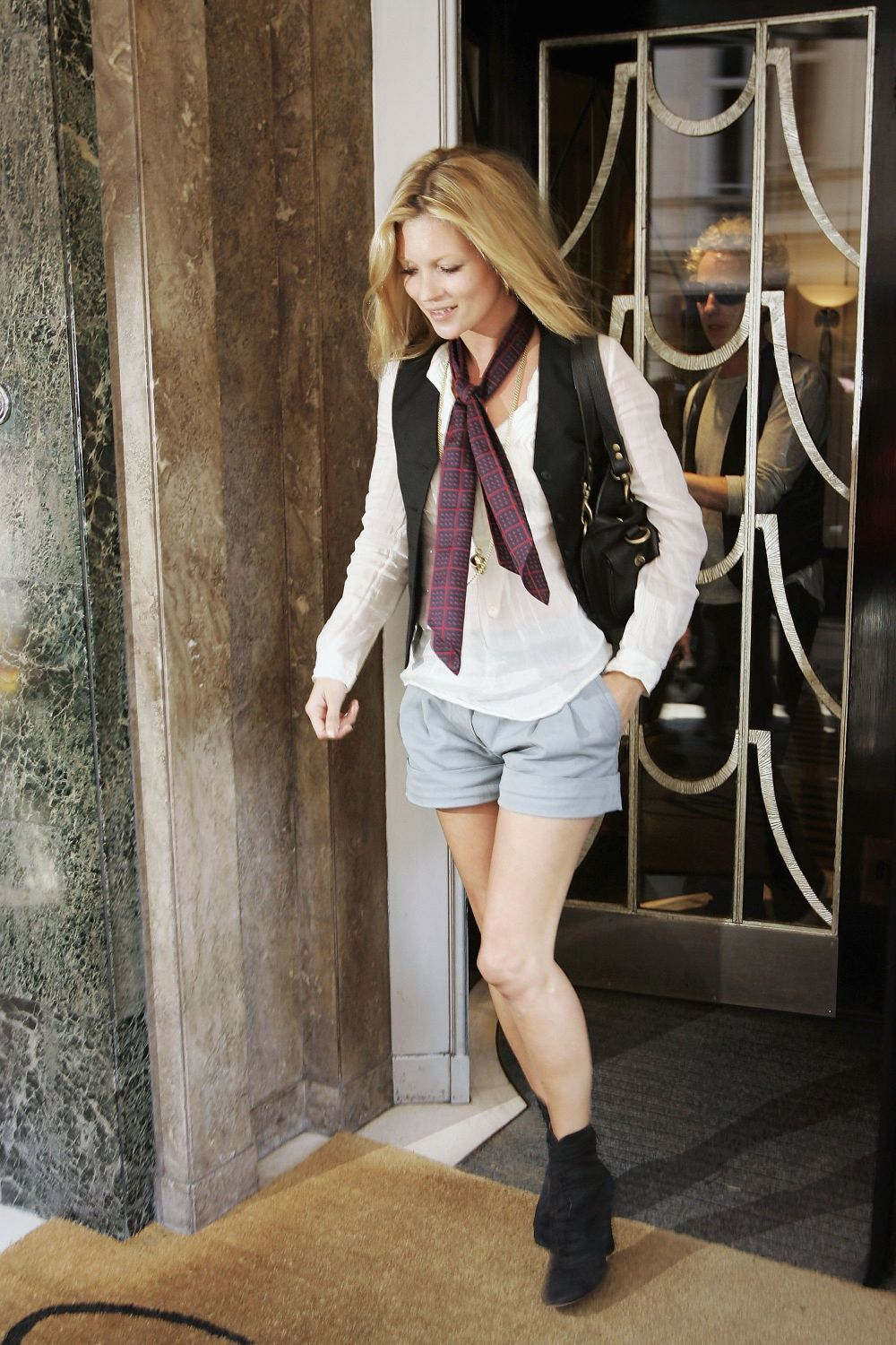 Kate Moss con chaleco y shorts.