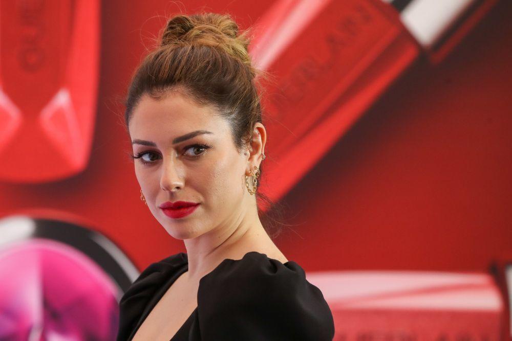 La actriz acompañó su maquillaje de labios rojo con un moño alto efecto deshecho enfundada en un vestido negro corto de manga abullonada.