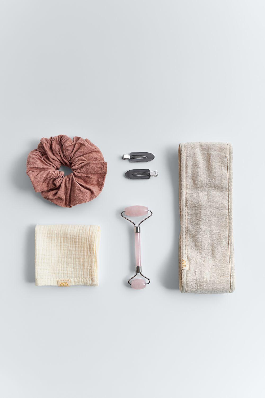 El neceser incluye un coletero con goma elástica, una diadema ajustable con tiras adherente, una toallita de algodón, pinzas para el pelo que no dejan marca y un rodillo de cuarzo rosa para masajear el rostro y el cuello.