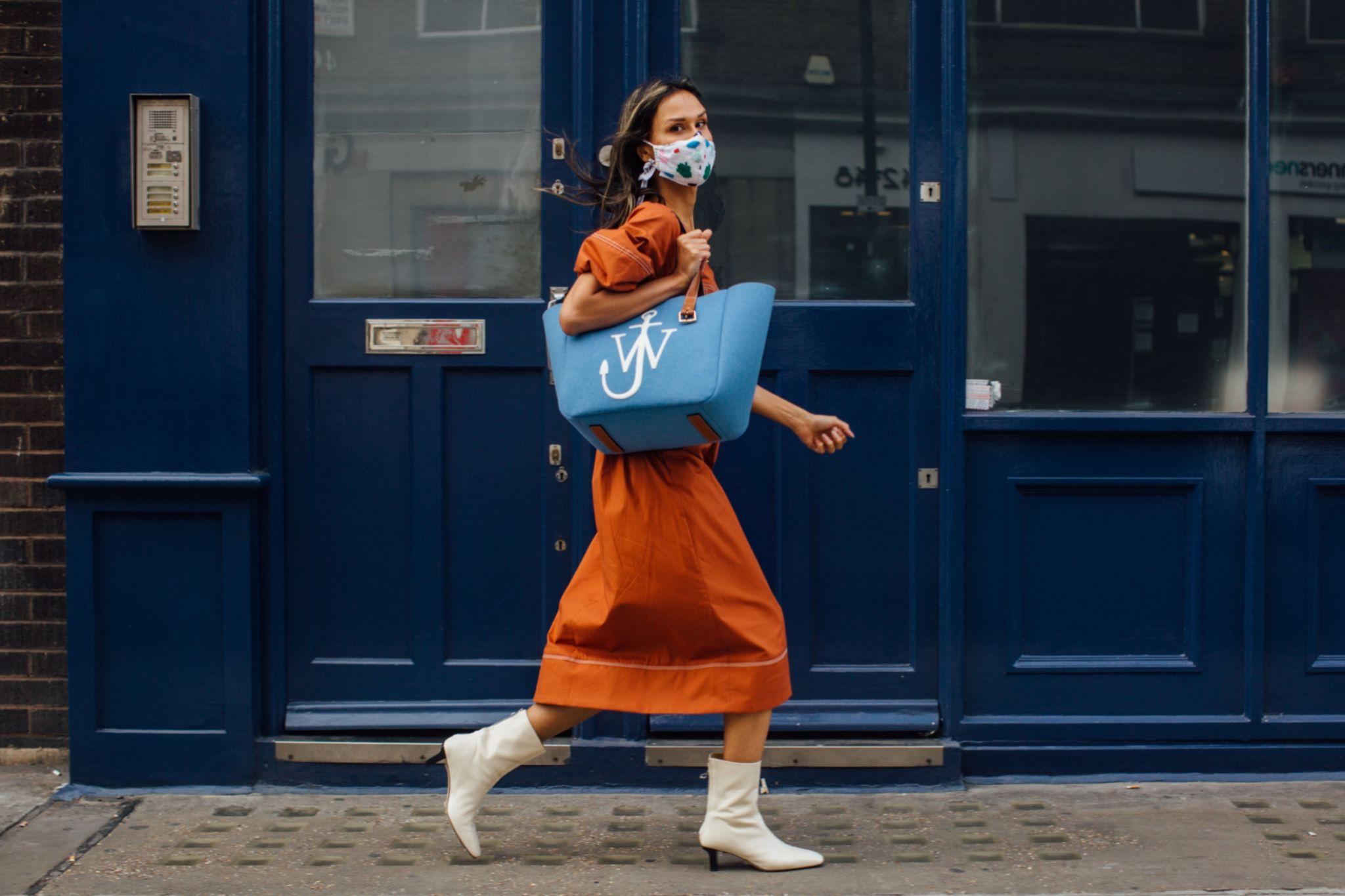 Bota blanca en las calles de Londres, con shopping bag de JW Anderson.