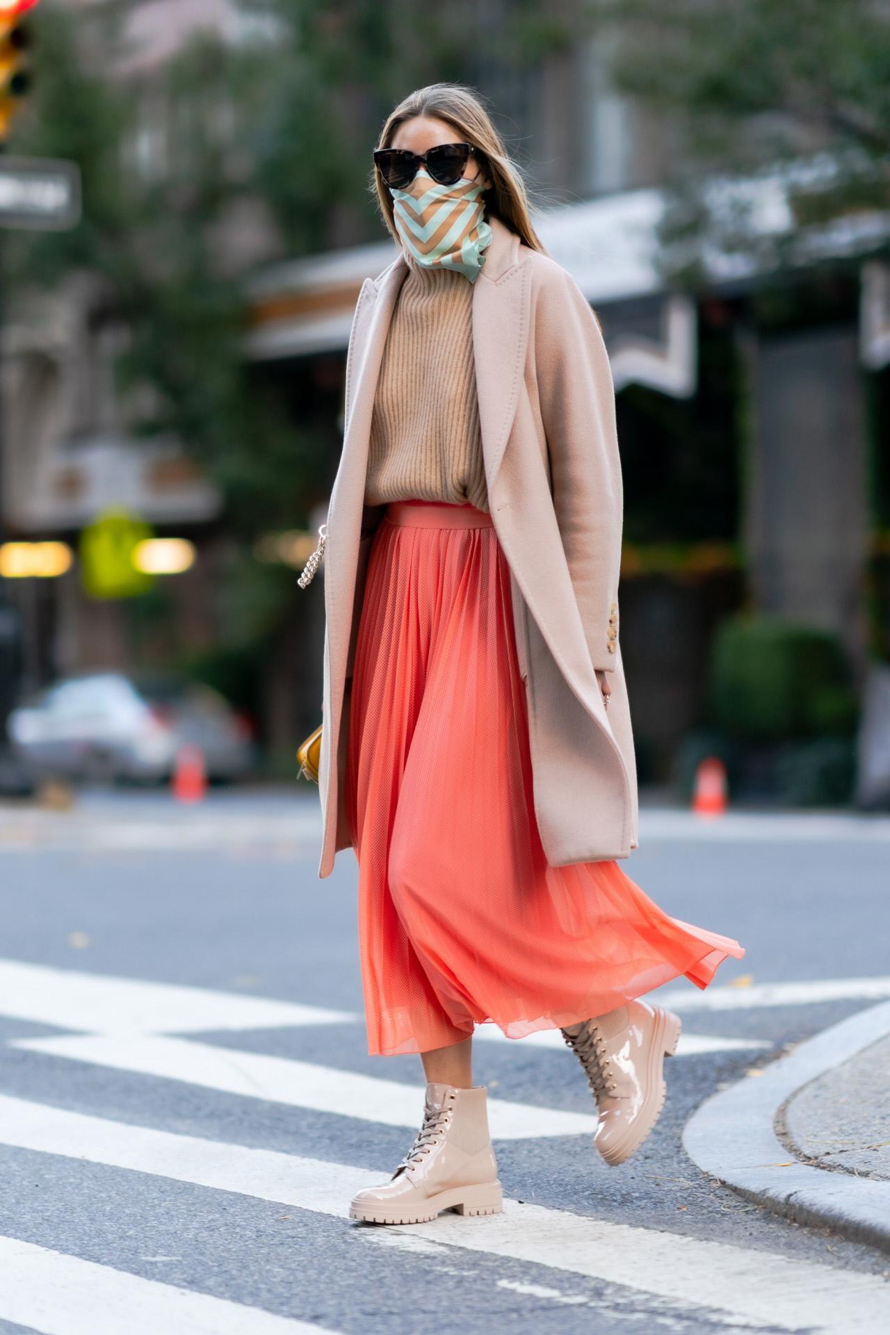 Olivia Palermo con una falda plisada y botas nude de cordones.