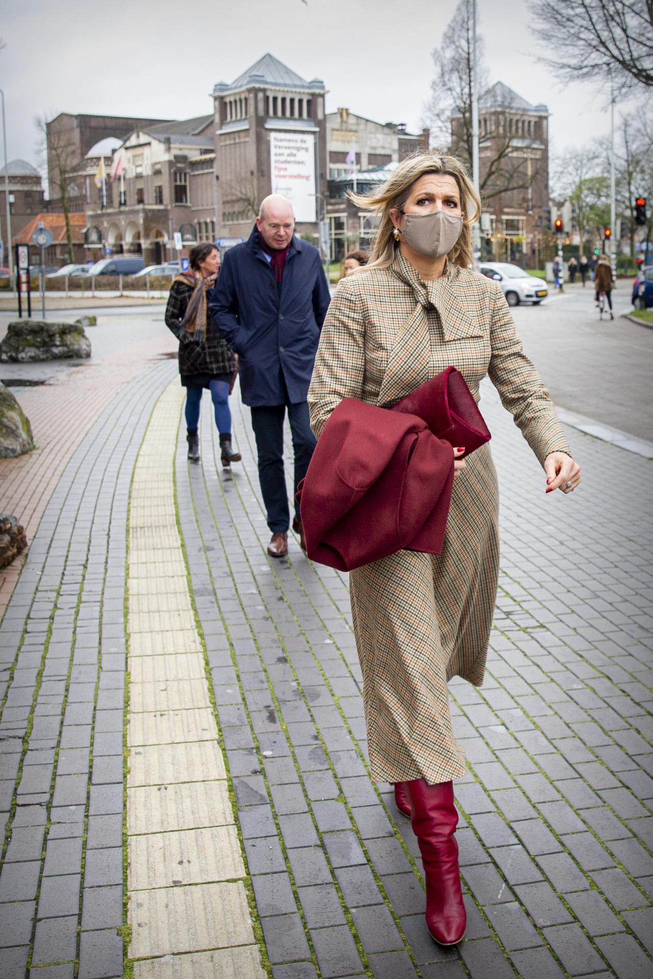 Máxima de Holanda con vestido de cuadros y botas rojas.
