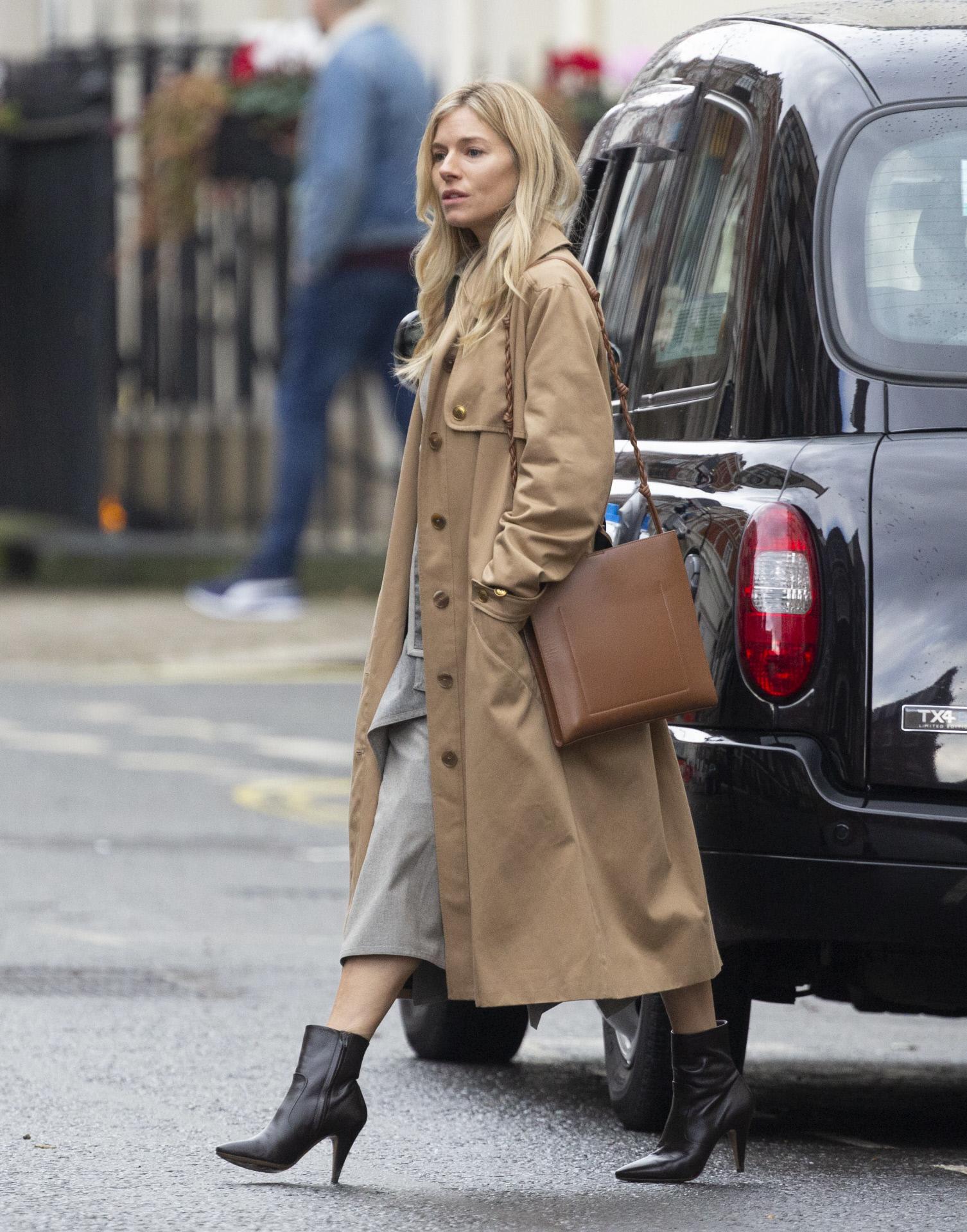 El look de Sienna Miller con botines negros y vestido midi.