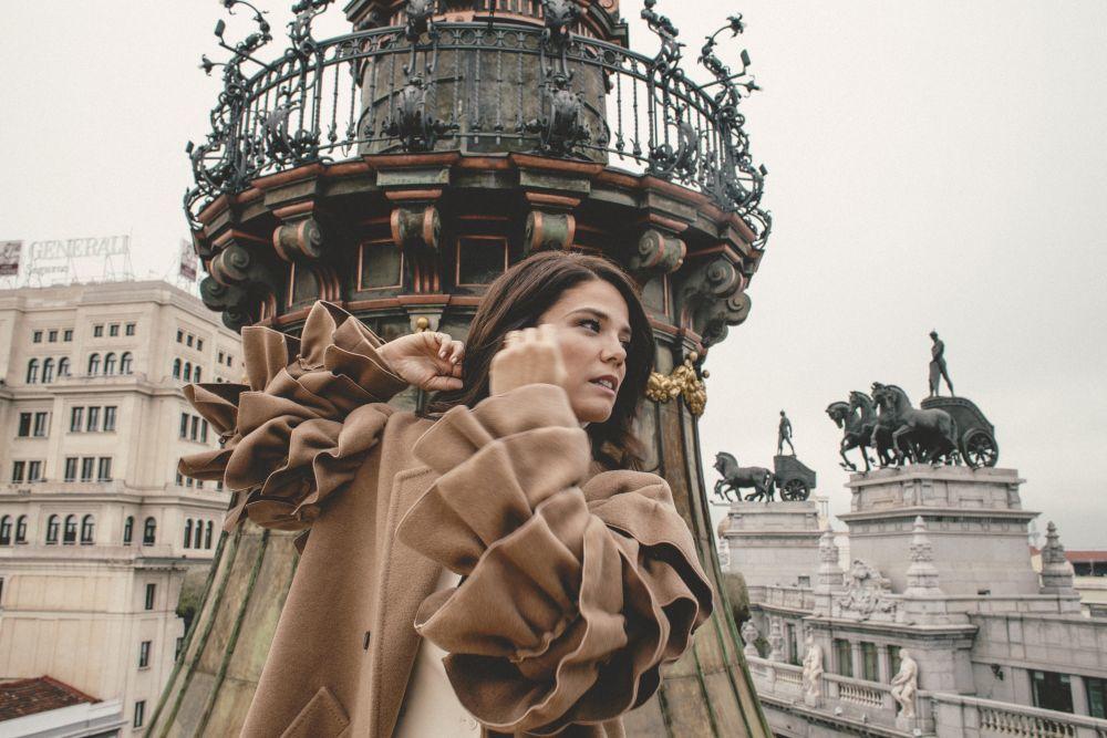 Juana Acosta en la terraza del Hotel Four Seasons con abrigo con mangas con volumen beige y bermuda, ambos de Max Mara, y jersey de cuello vuelto, de Mango.