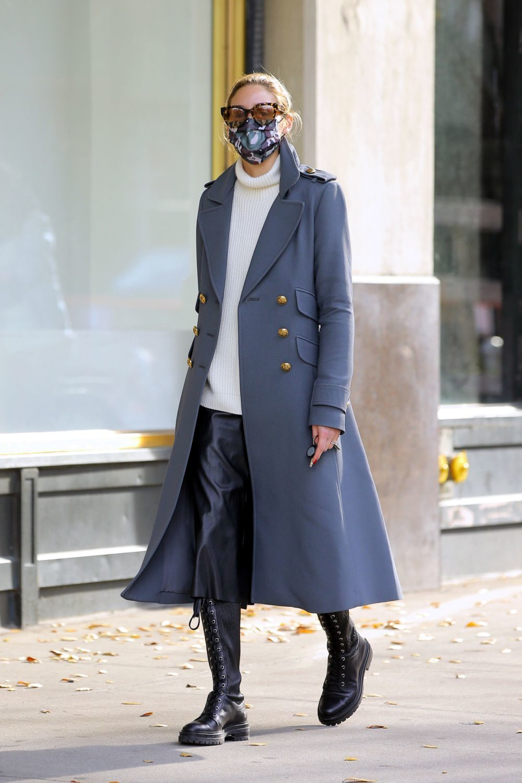 Olivia Palermo con abrigo army con botonadura y bolsillos y botas altas de suela gorda y cordones.