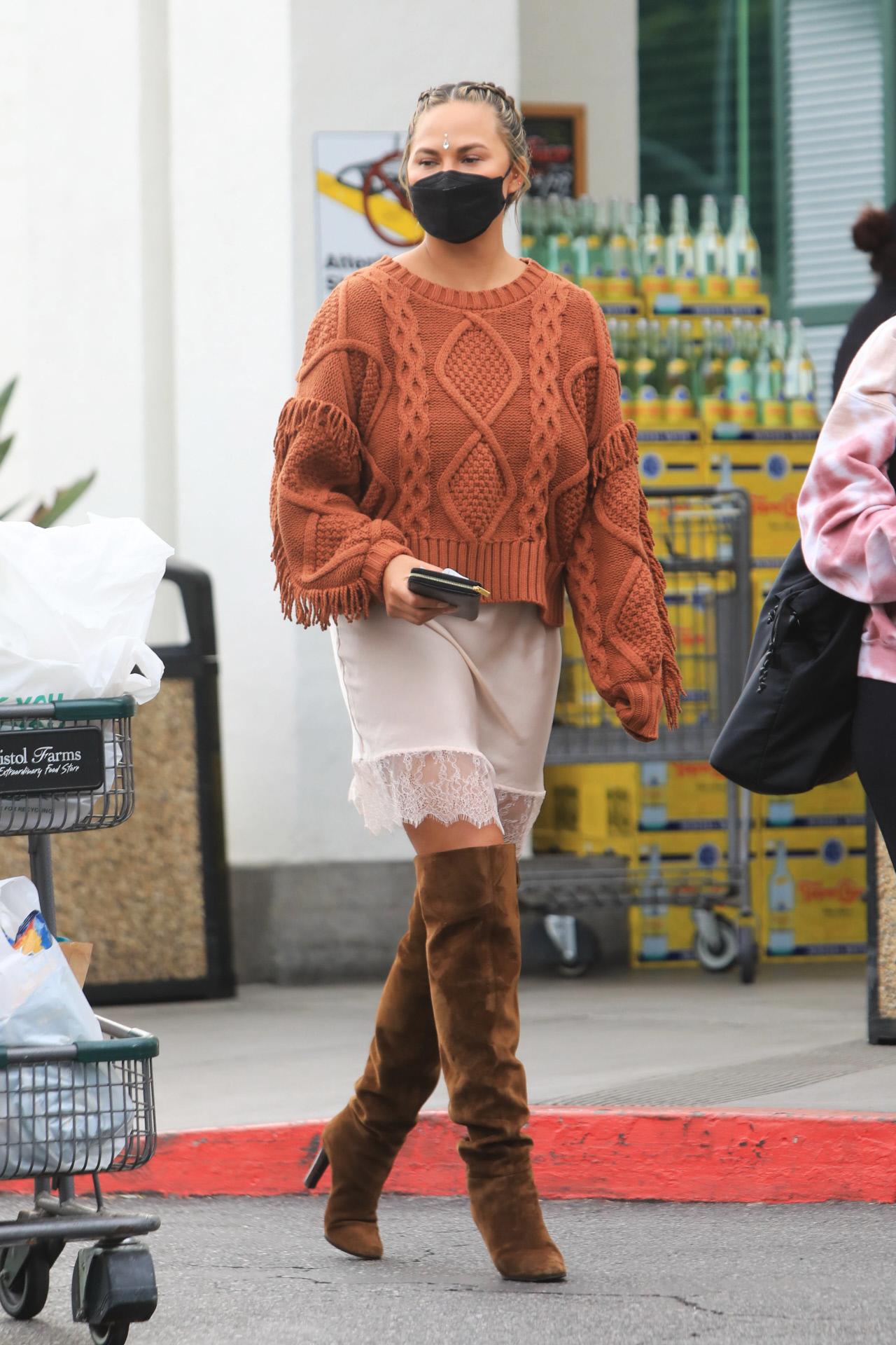 Chrissy Teigen con vestido y botas altas.
