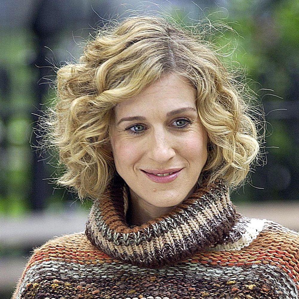 Carrie con su melena midi rizada con capas y mechas buttery blonde.