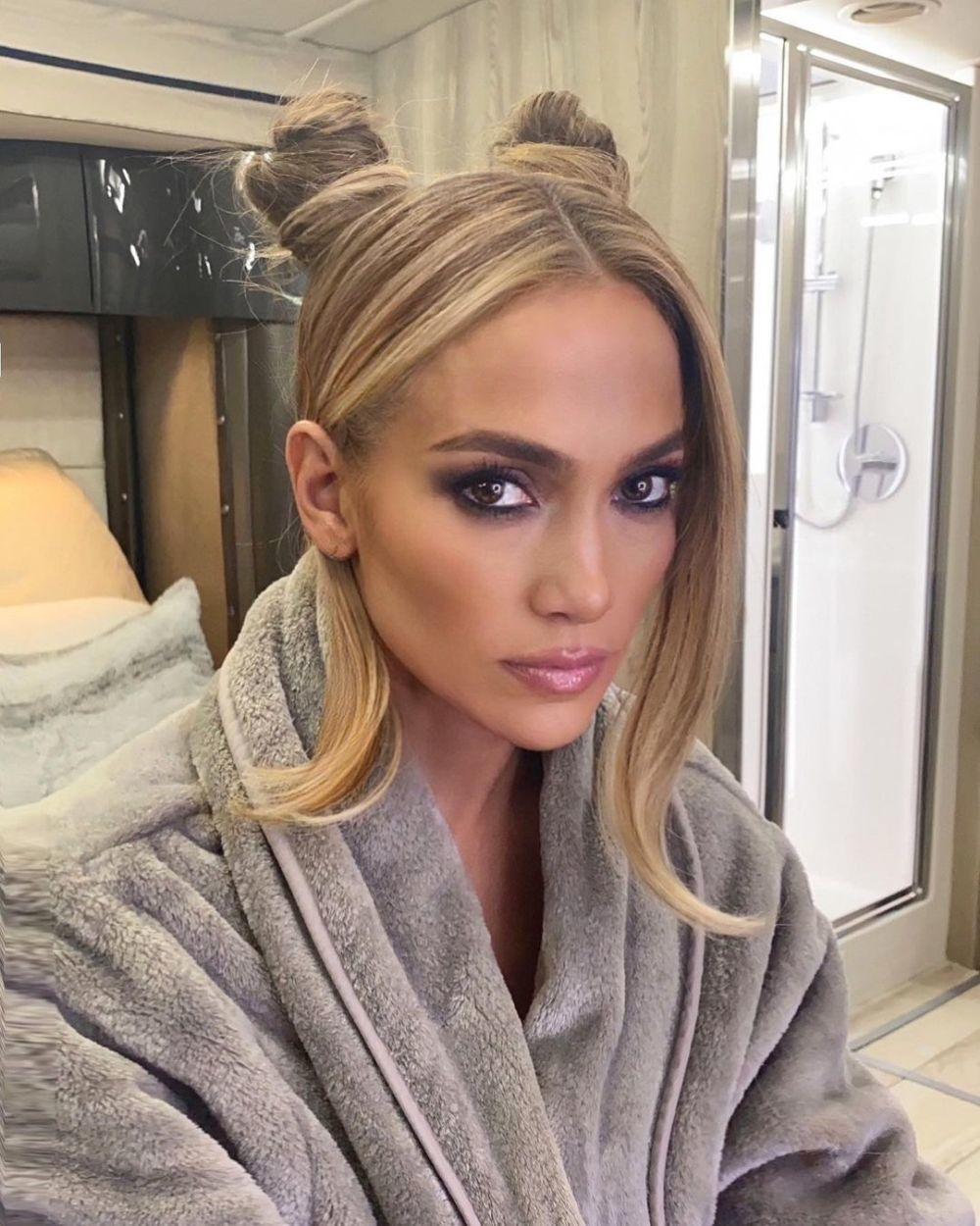 Jennifer Lopez luciendo unos space buns o doble moño sobre su pelo largo con mechones sueltos y con mechas chunky.