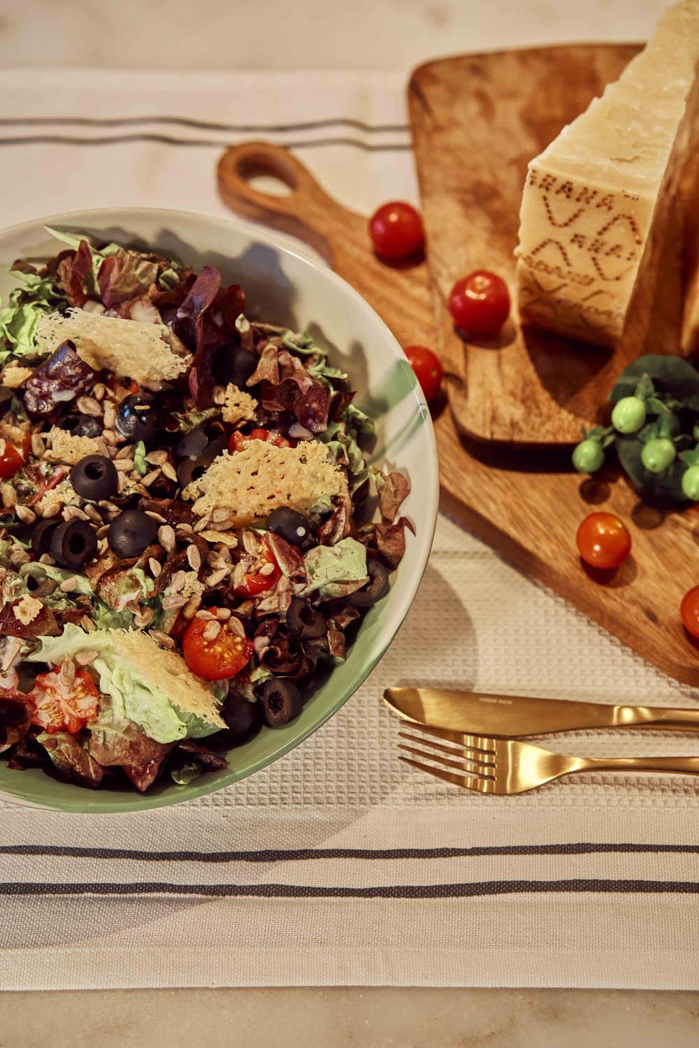 Ensalada de primavera con crackers de Grana Padano, una receta ligera y deliciosa, ideal para el buen tiempo. Créditos: mantel y tabla de madera de Zara Home.