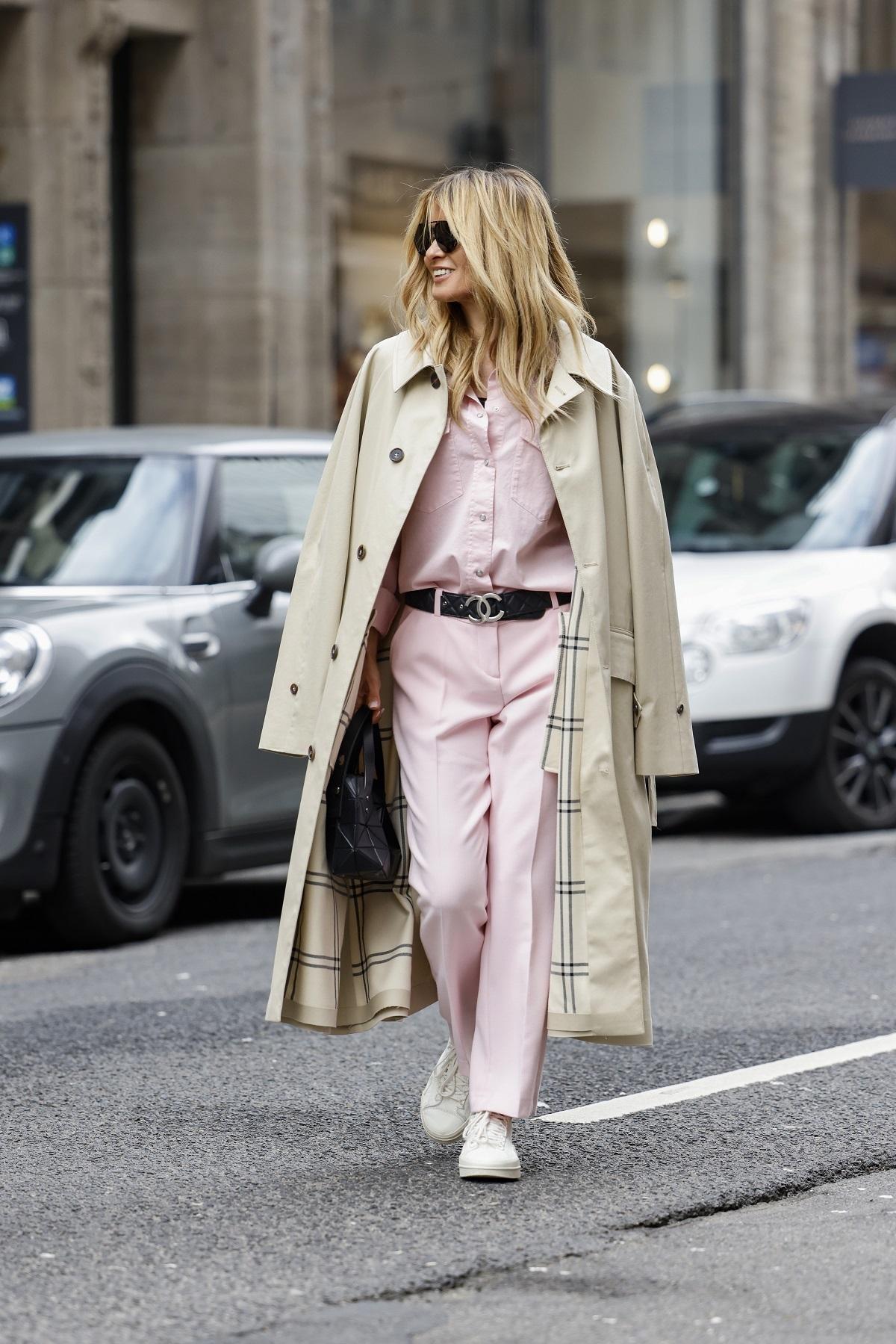 Una invitada a los desfiles con trench y pantalones rosas.