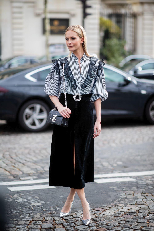 Poppy Delevingne con camisa de rayas y falda negra.