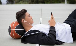 Chico tumbado en cancha baloncesto