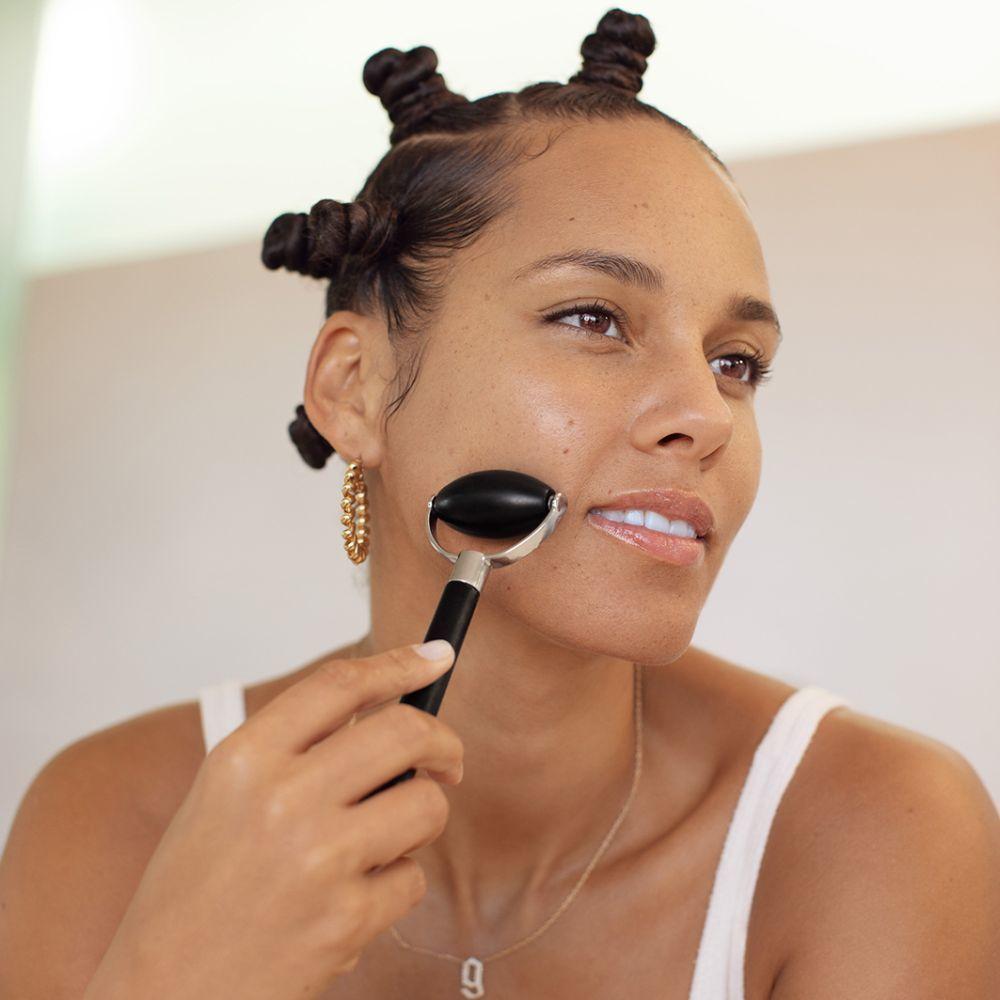 Alicia Keys con el masajeador de obsidiana para estimular los músculos faciales, muy fácil de usar.