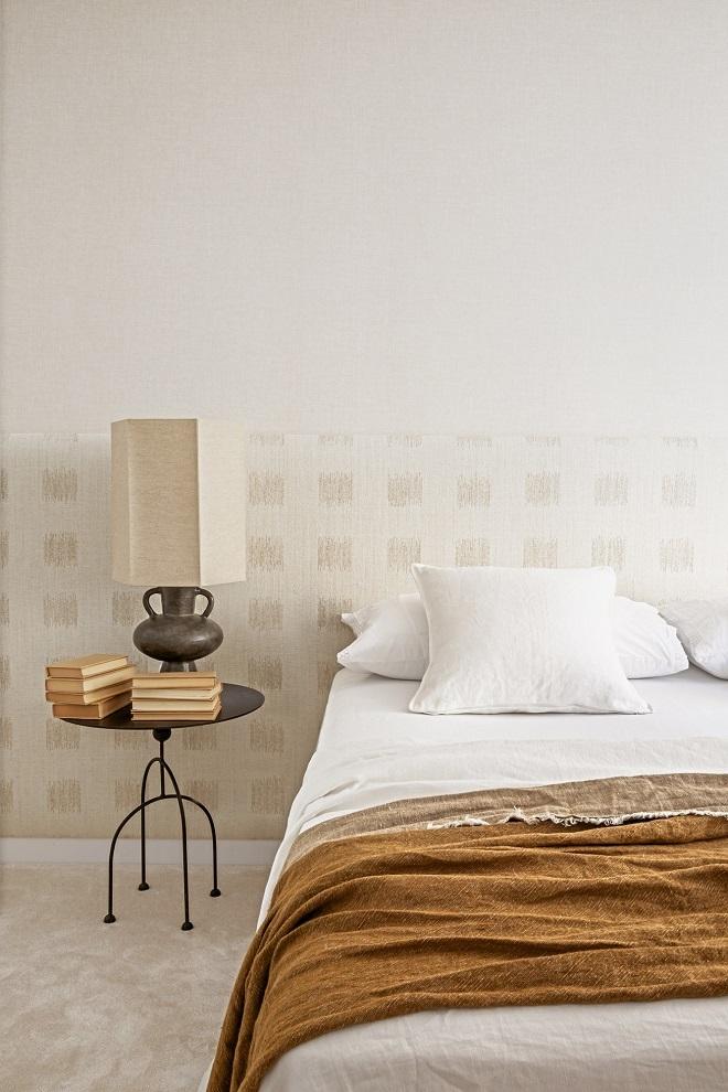 El dormitorio, con mesilla de noche de Tristán Domecq; lámpara de Rue Vintage 74; colcha y almohadones de Alhambra, y plaid, Rue Vintage 74. El cabecero corrido lleva tela de James Malone, Living Valdemarín.