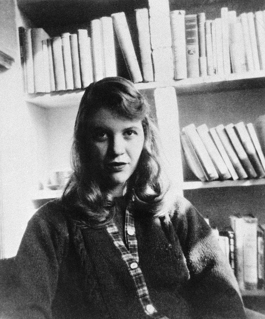 Sylvia Plath sentada frente a su librería en los años 50.