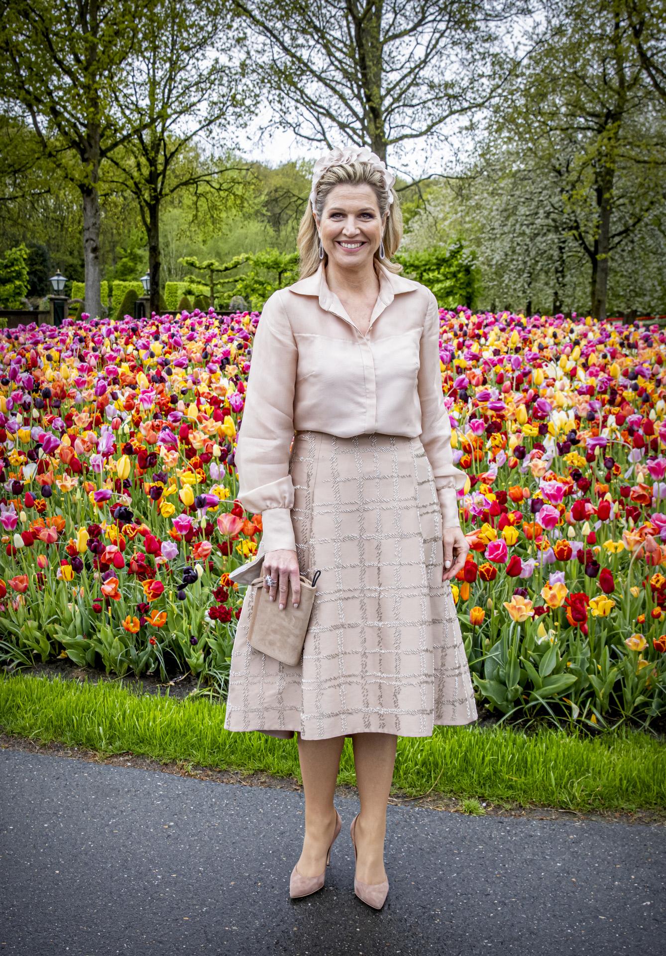 Máxima de Holanda con un jardín de tulipanes a su espalda.
