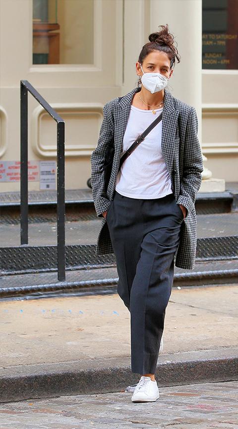 Katie Holmes con pantalón de pinzas y zapatillas blancas.