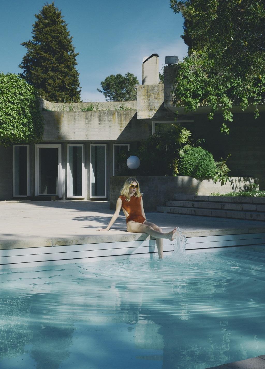 Enmarcada dentro de unos de los ejemplos más representativos de la arquitectura brutalista de los 60 en España, la Casa Carvajal, la modelo lleva body de punto de seda de Hermès y gafas de sol de Dolce & Gabbana.