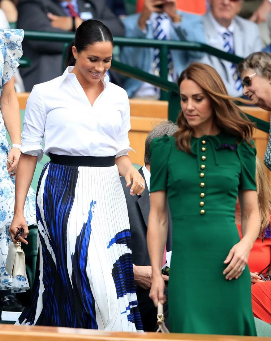 El look de Meghan Markle, con falda plisada y camisa blanca.