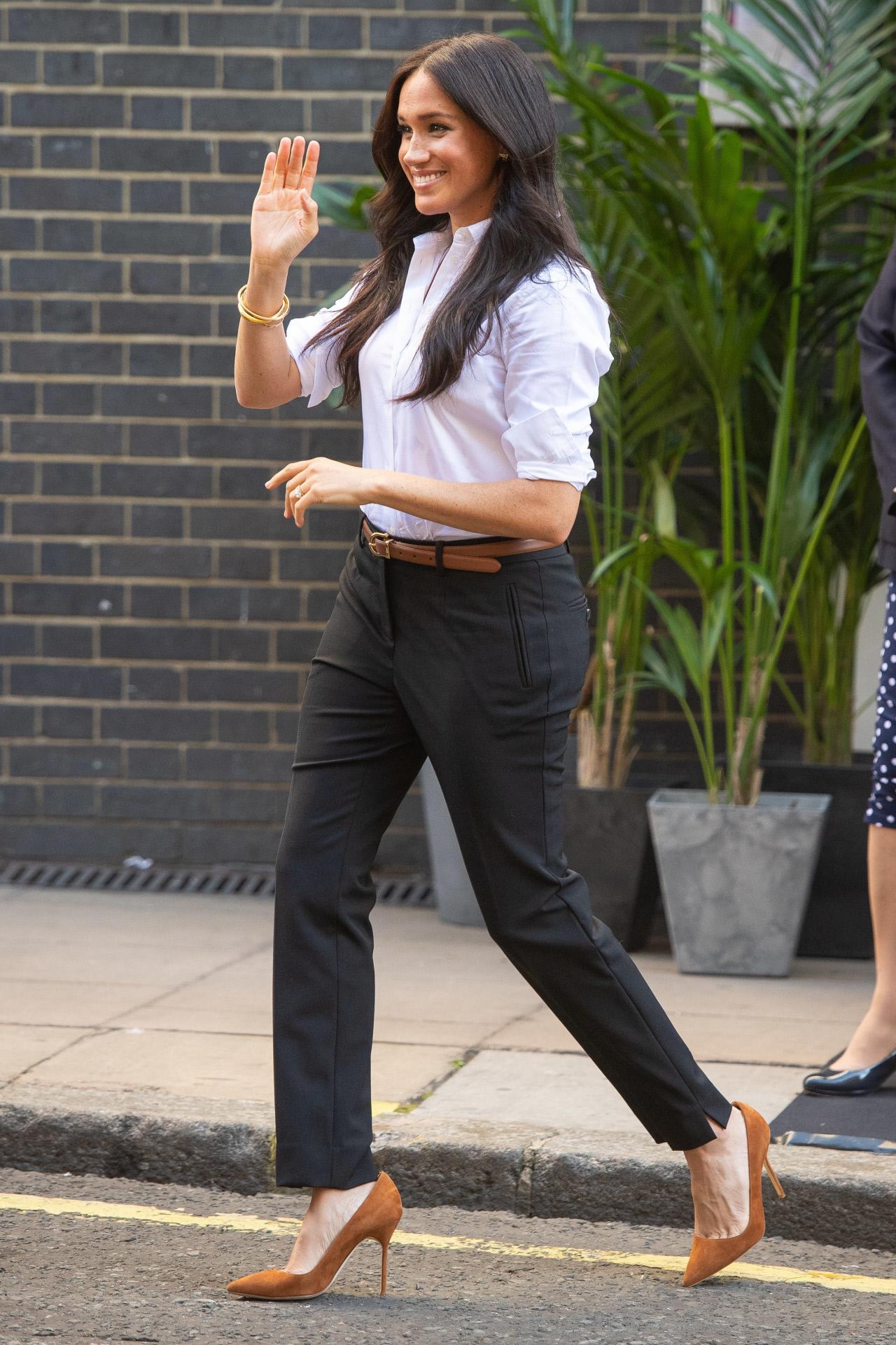 La duquesa de Sussex combina la camisa clásica con pantalones negros.