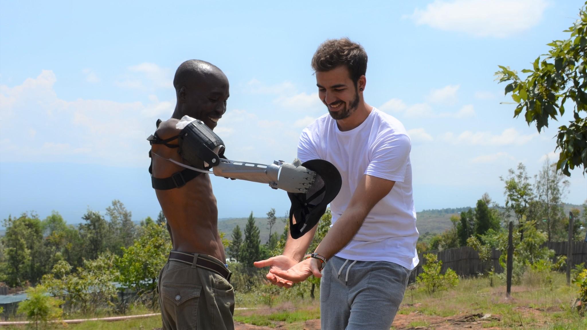 Guillermo Martínez en Kenia enseñando a utilizar uno de sus brazos 3D a un chico de allí.