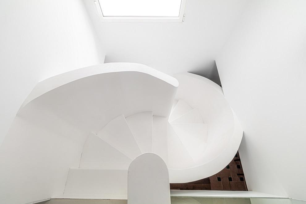 La escalera es un diseño de las interioristas de hierro y pladur, y está  pintada de blanco.