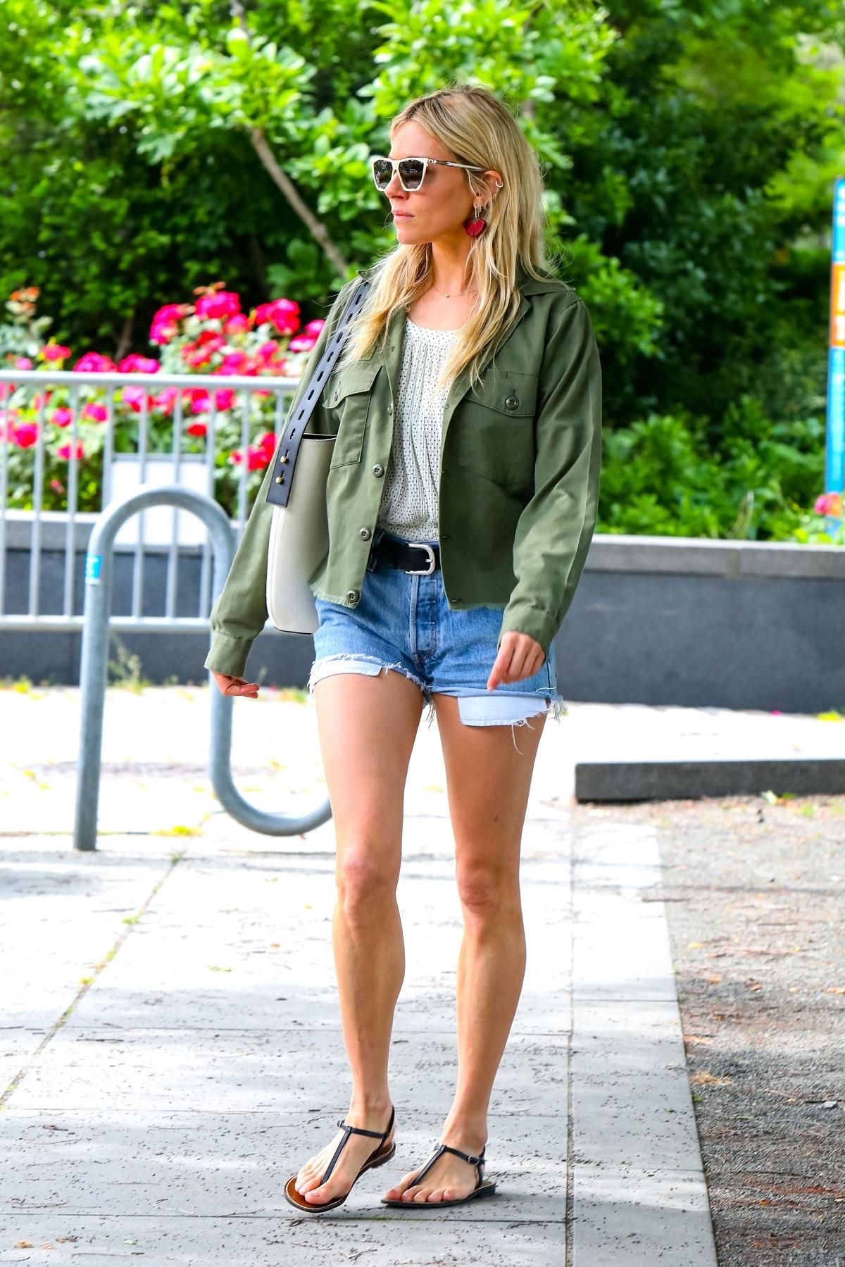 Sienna Miller con shorts y sandalias planas.