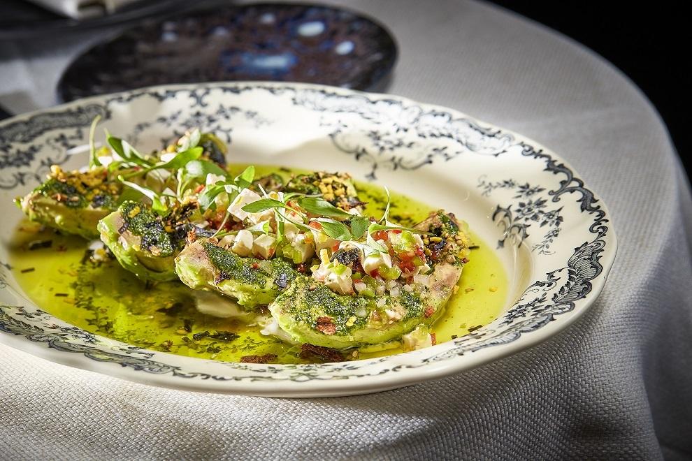 Aguacate a la brasa, pesto de cilantro joven y queso Feta.