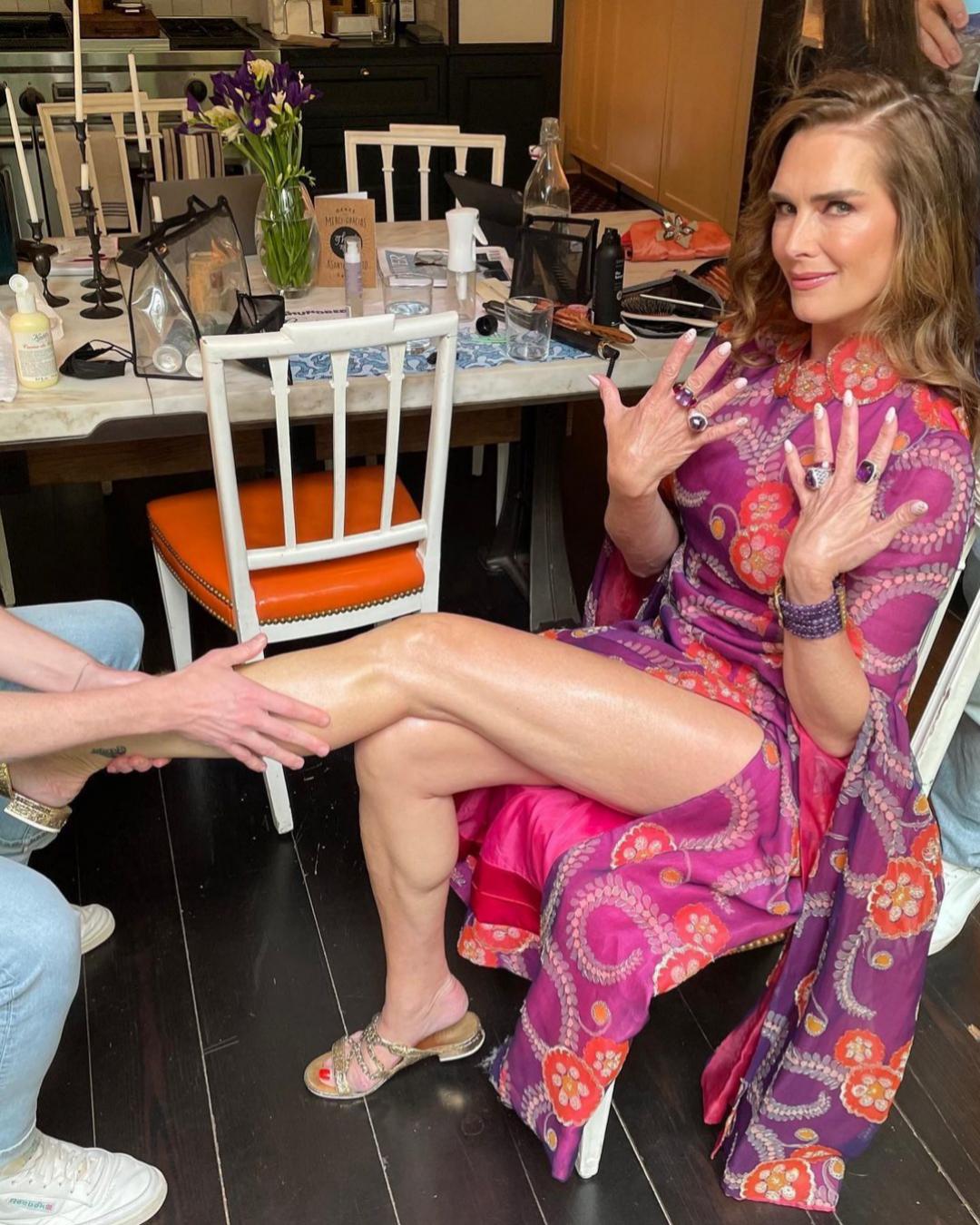 Brooke Shields haciéndose la manicura en tonos blancos y la pedicura en rojo.
