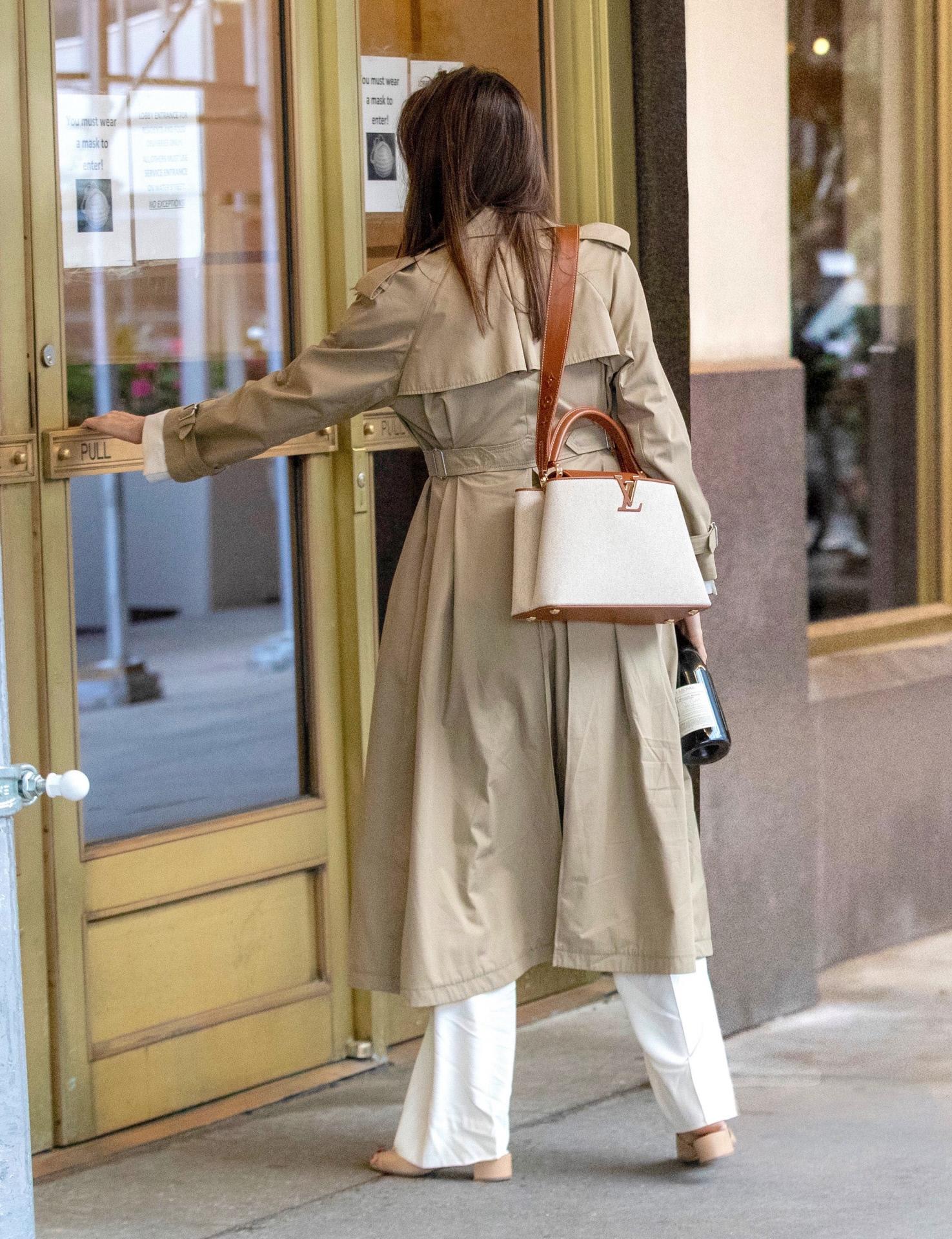 Angelina Jolie combinó el sastre blanco con una gabardina y un bolso de Louis Vuitton.