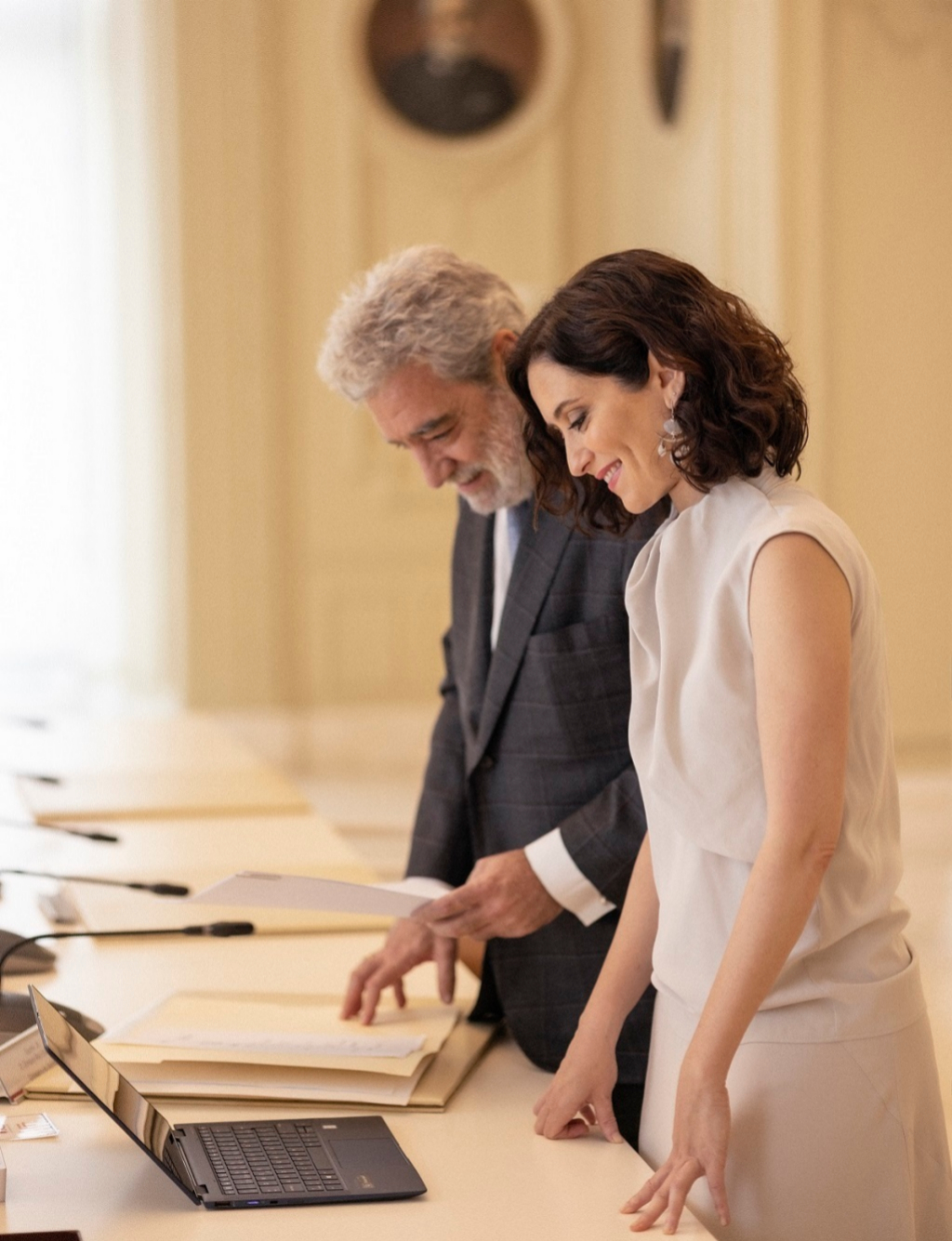 La presidenta despachando con su jefe de Gabinete Miguel Ángel Rodríguez (M.A.R). Ella lleva top de seda gris con falda a juego, Maksu y pendientes, Aristocrazy.