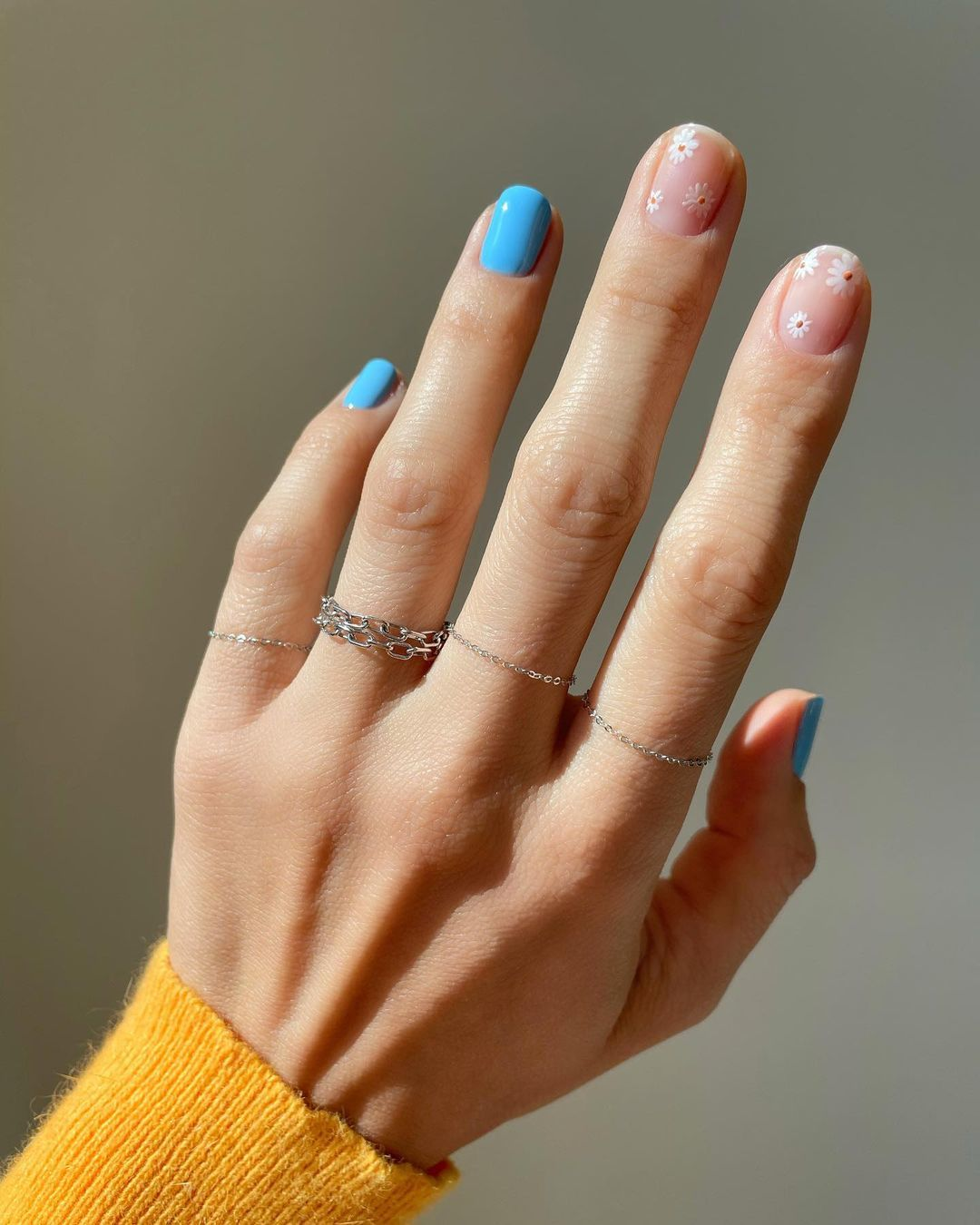 Los motivos de flores intercalados con colores tendencia como el azul son tendencia para tus uñas esta verano.