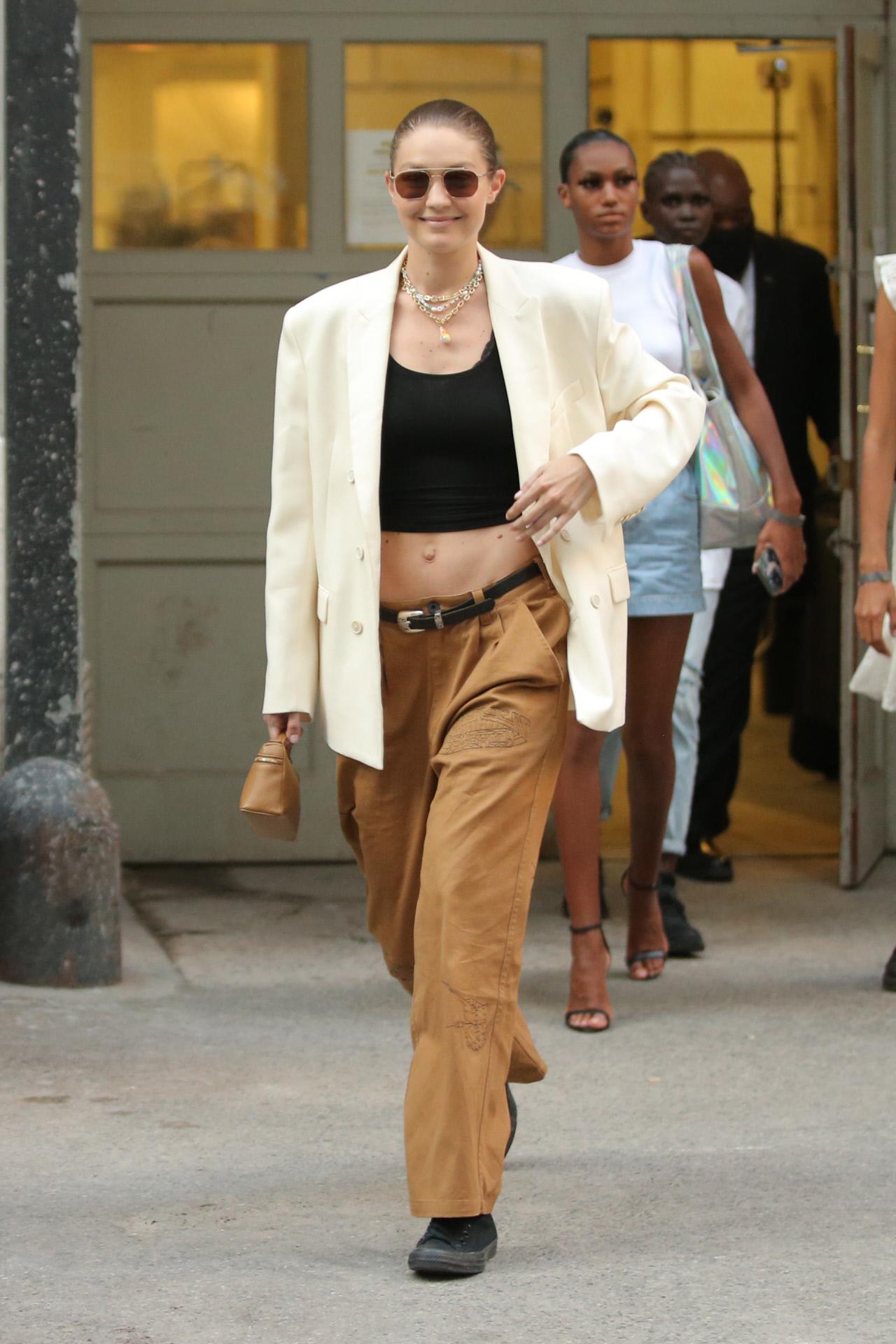 Gigi Hadid, con pantalones masculinos tipo cargo en caqui, top negro y blazer oversize en blanco, a su salida del desfile de Marc Jacobs.