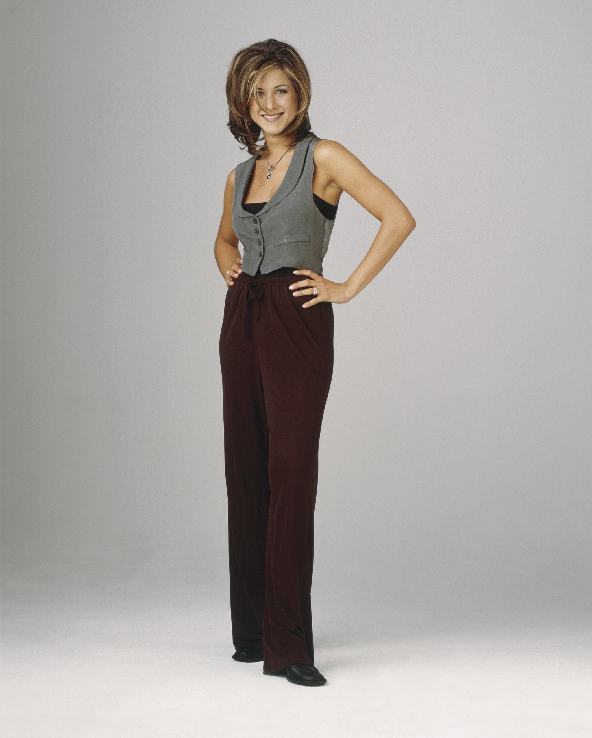 Jennifer Aniston con chaleco y pantalones de pinzas.