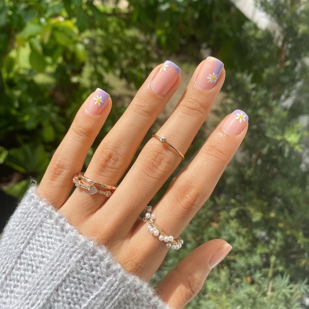 Uñas con flores pintadas guiños a la manicura francesa en tonos lilas y base nude.
