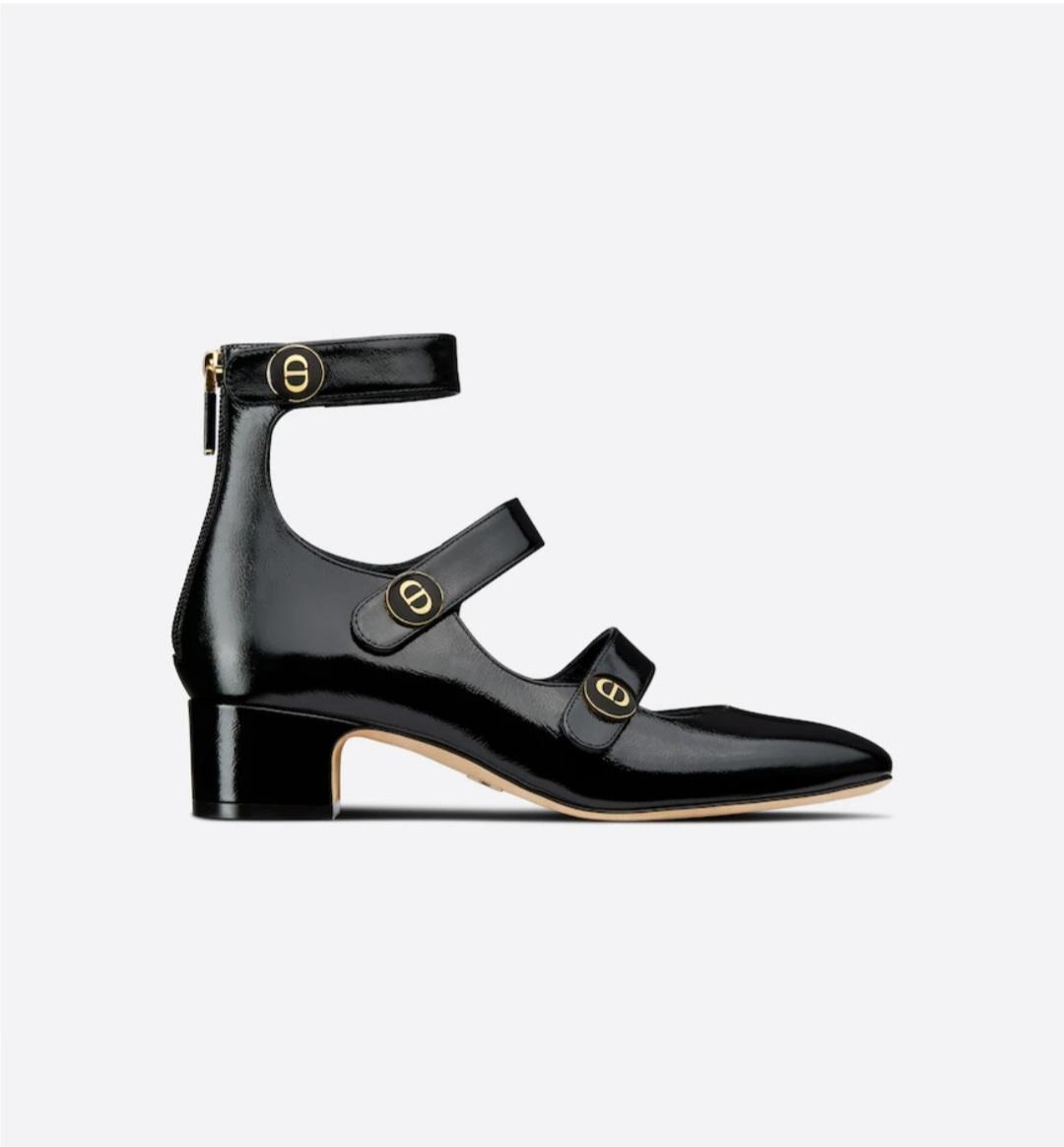 Zapatos salón D-Doll de Dior en piel de becerro brillante negra con la puntera levemente cuadrada y tres tiras con botones de esmalte negros con la firma CD dorada. Completa este elegante zapato el tacón de bloque de 4 cm.