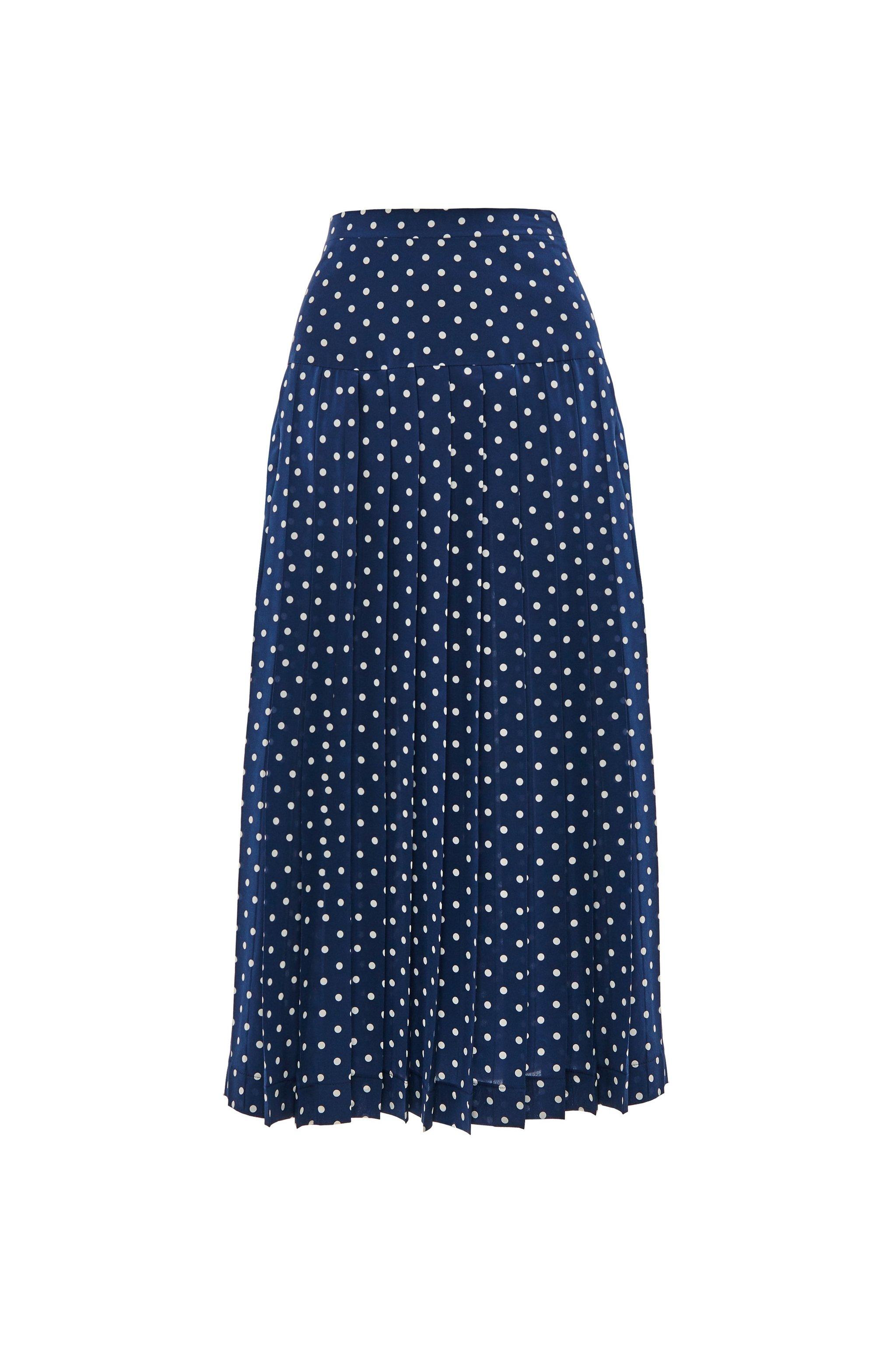 La falda plisada de lunares blancos sobre fondo azul marino en tejido de seda de Alessandra Rich (622 euros).