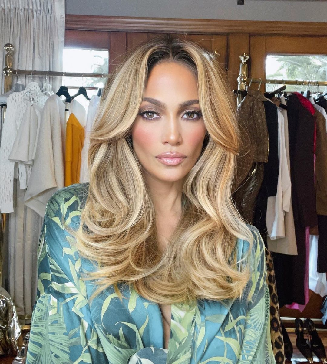 Jennifer Lopez con un flequillo abierto y una melena a todo volumen muy años 70 de la mano del estilista Chris Appleton.