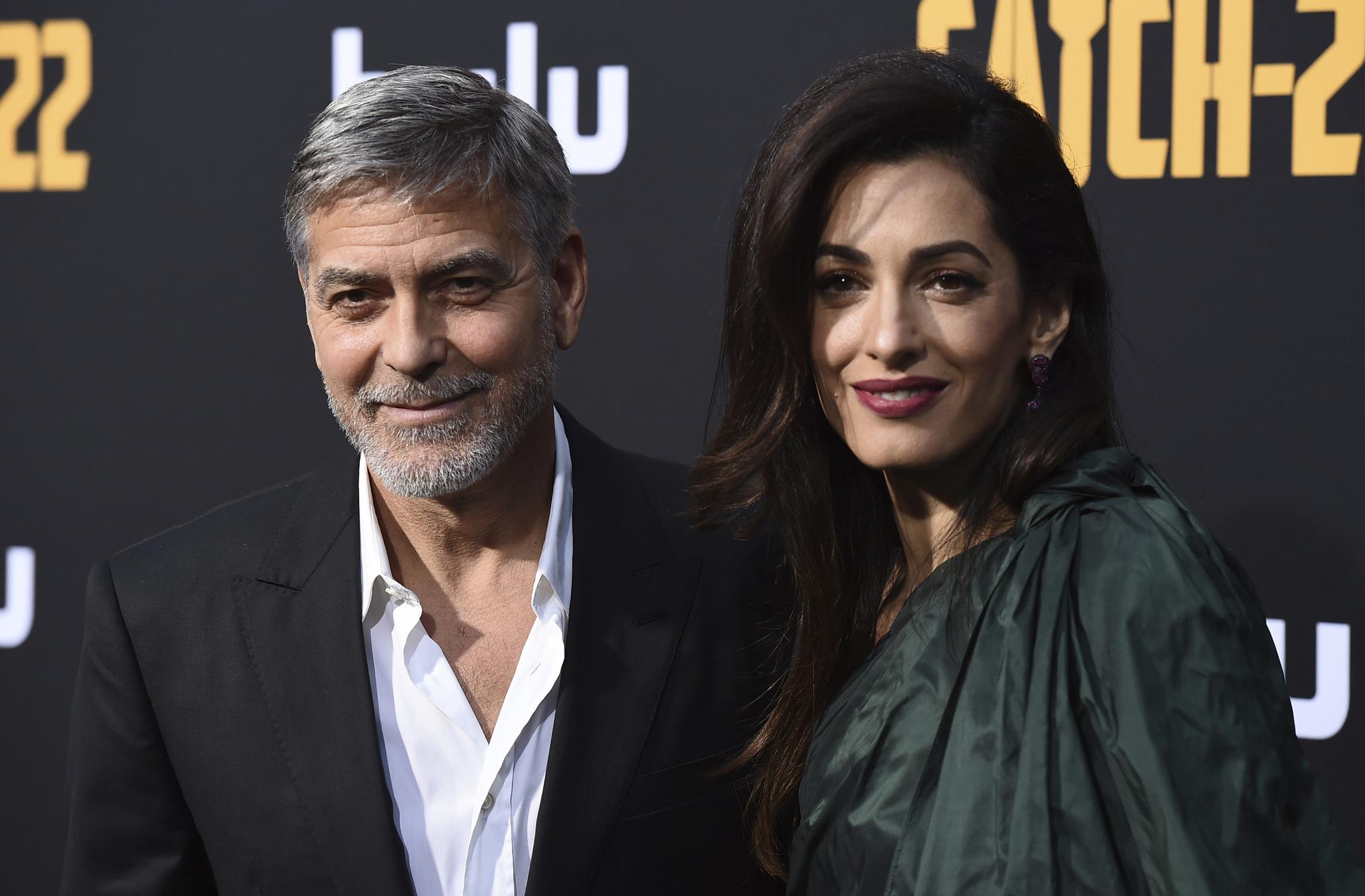 George Clooney con su pelo con canas y barba junto a su mujer, Amal.