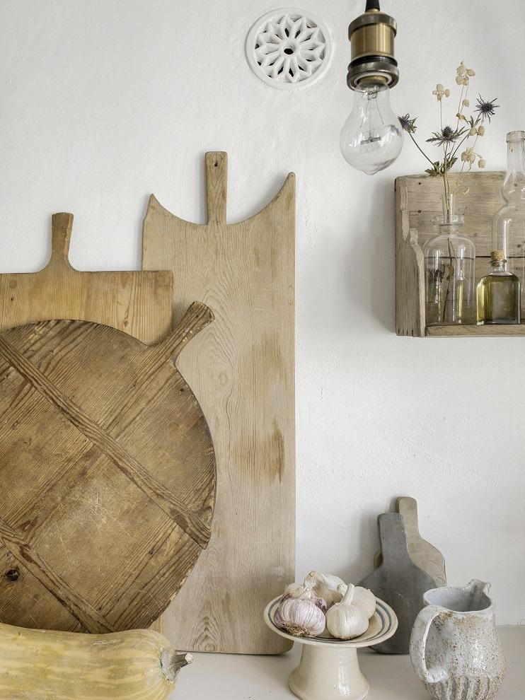 En este detalle del comedor, tablas antiguas de madera para pizza, de Viveca, y de piedra natural de Alma Design. Plato de Santa María y jarra de Grace Alzamora. La lámpara es de Illum Bolighus (Oslo).