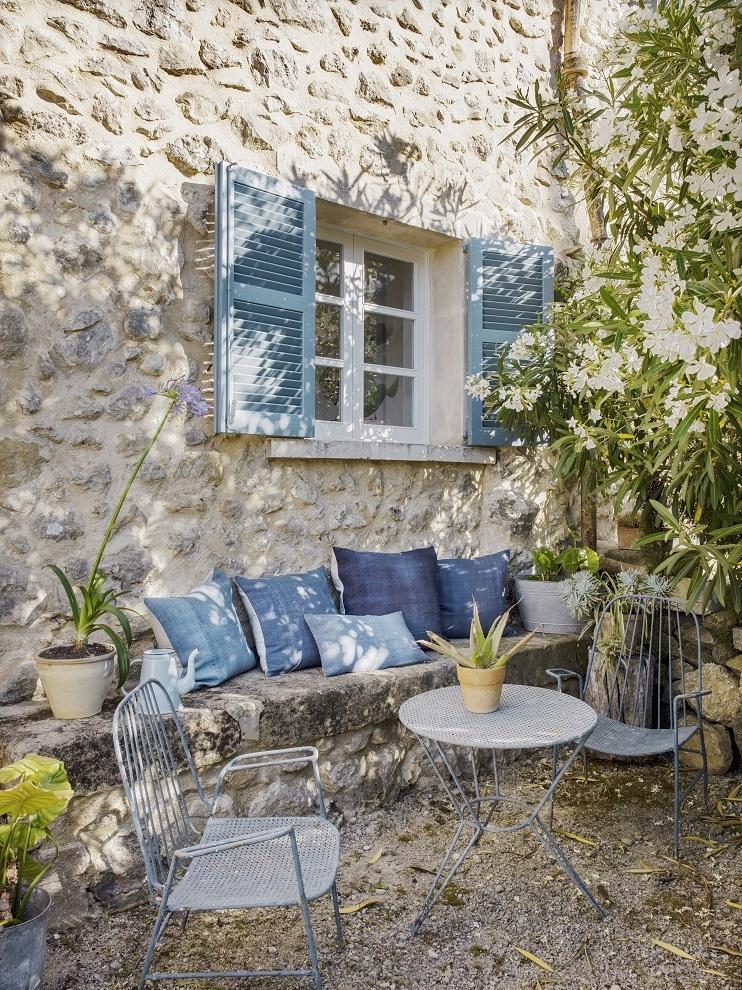 En este rincón del jardín, almohadones pintados a mano por Espanyolet, sobre lino vintage. Muebles de In Progress Palma.