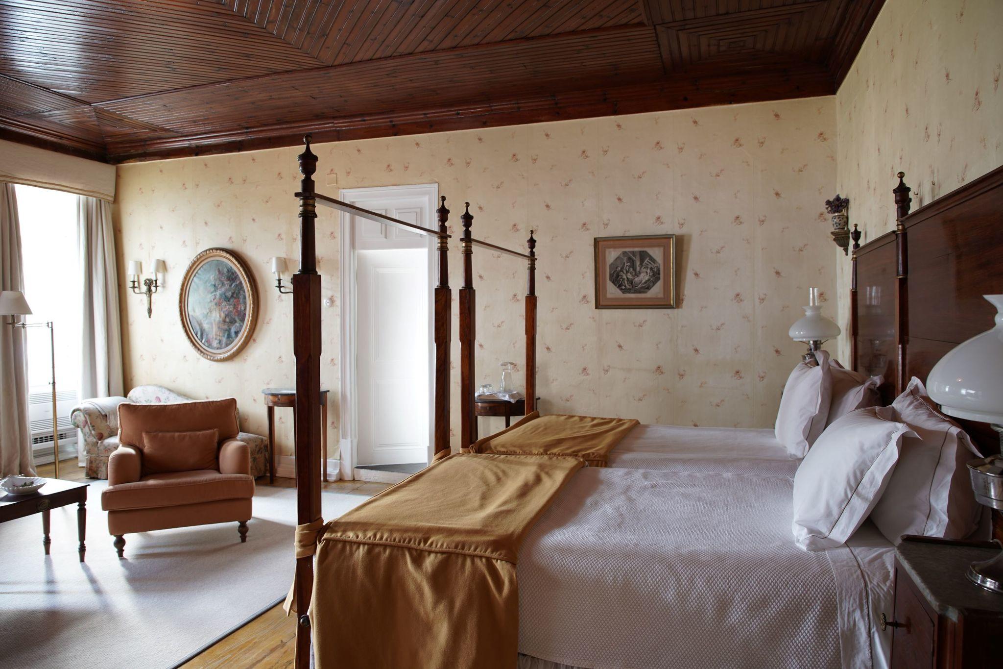 Una de las habitaciones del hotel, con un delicado papel pintado y techos de madera.