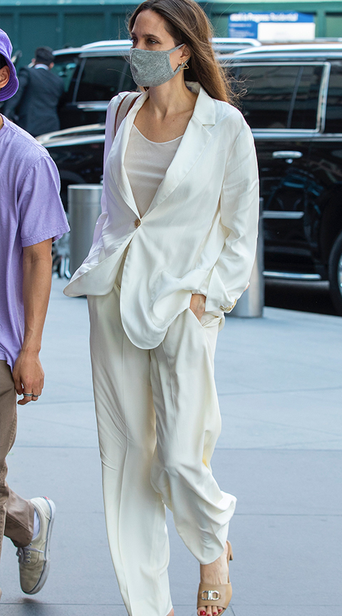 Angelina Jolie in a white suit jacket.