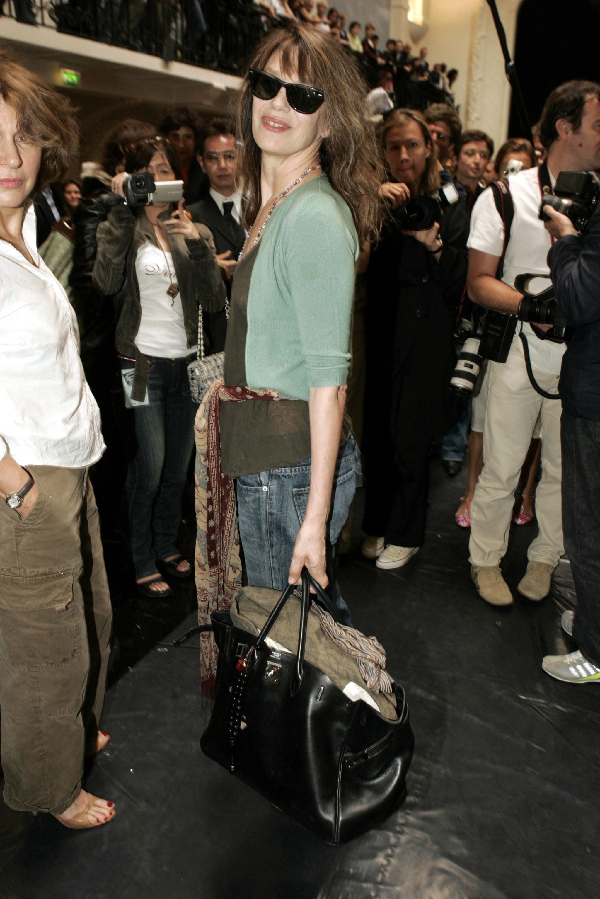 Jane Birkin acudiendo al desfile de Jean Paul Gaultier en París en 2004 con el bolso de Hermès que ella misma ayudo a diseñar.