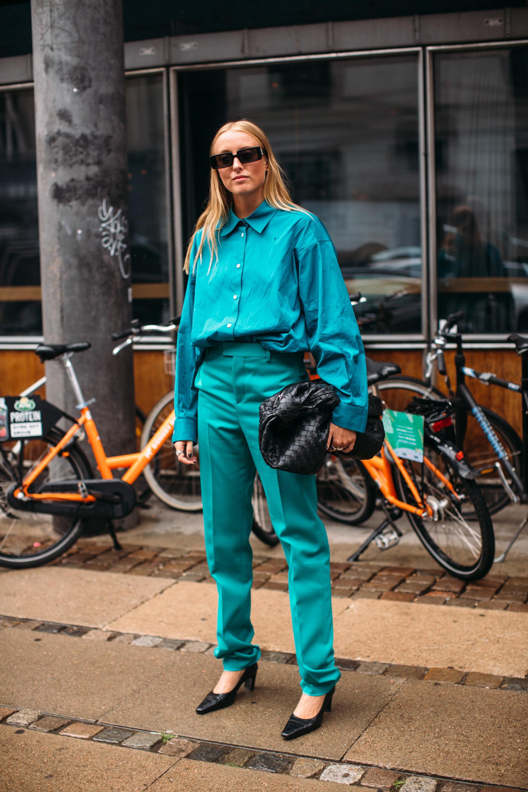 Total look verde azulado con accesorios negros.