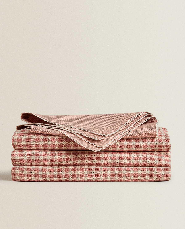 Mantel de algodón e hilo tintado con estampado de cuadros (29,99 euros) y servilletas Servilleta de algodón e hilo tintado con piping en forma de ondas (7,99 pack de dos). Zara Home.