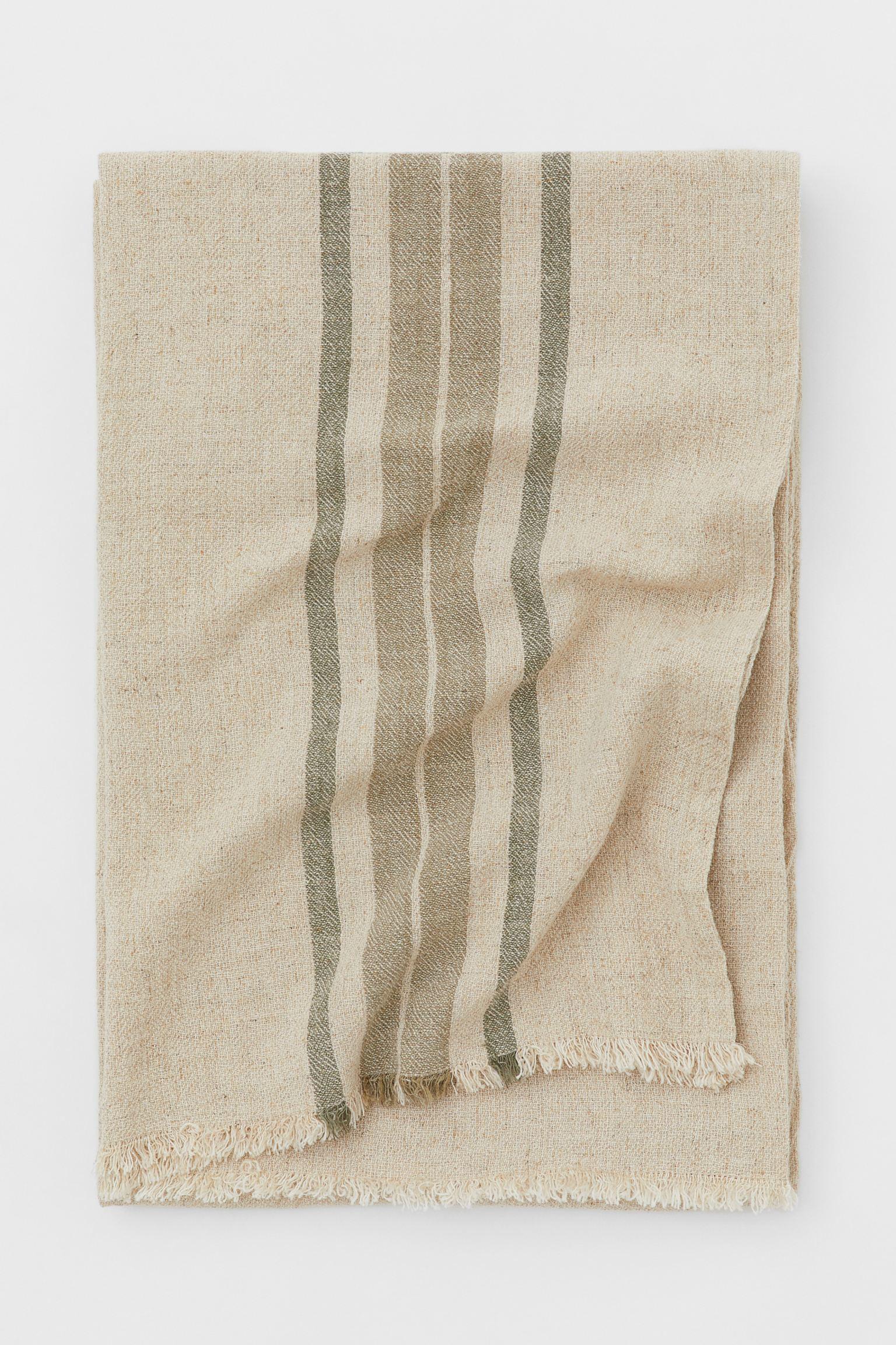 Manta en mezcla de lino. Manta en mezcla de algodón, viscosa y lino con rayas tejidas y acabado desflecado. H&M Home (34,99 euros).